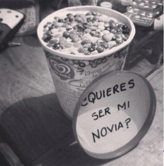 litro de nieve con dulces y escrito en tapa quieres ser mi novia