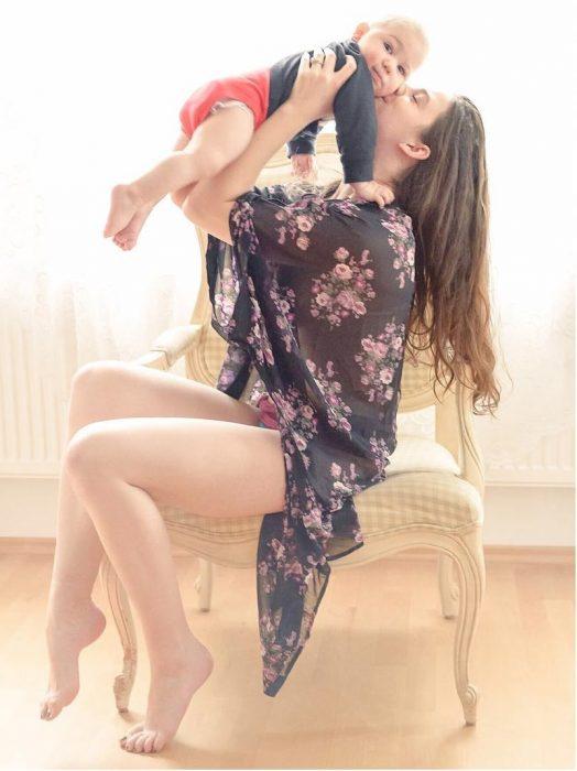 Chica besando a su bebé en la mejilla mientras lo sostiene por encima de su cabeza