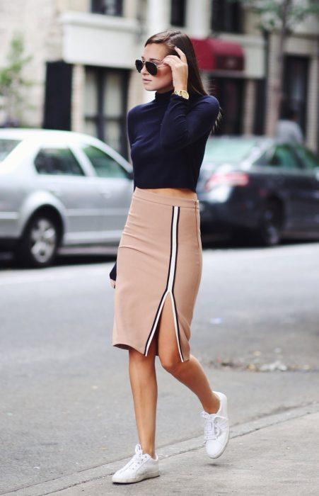Chica usando una falda de lápiz, crop top en color azul y zapatillas en color blanco