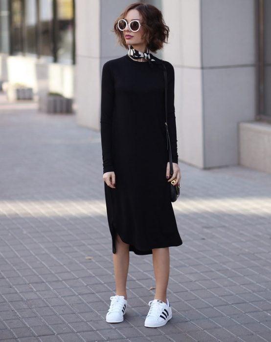 Chica usando un middi drees en color negro y zapatillas blancas