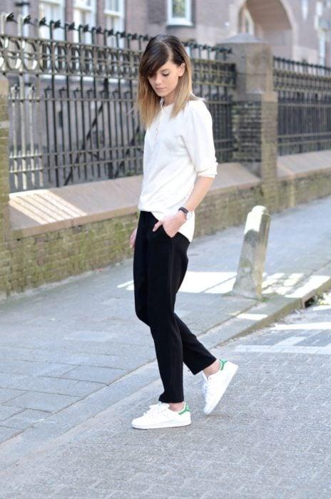 Chia usando una blusa blanca, pantalón negro y zapatillas blancas
