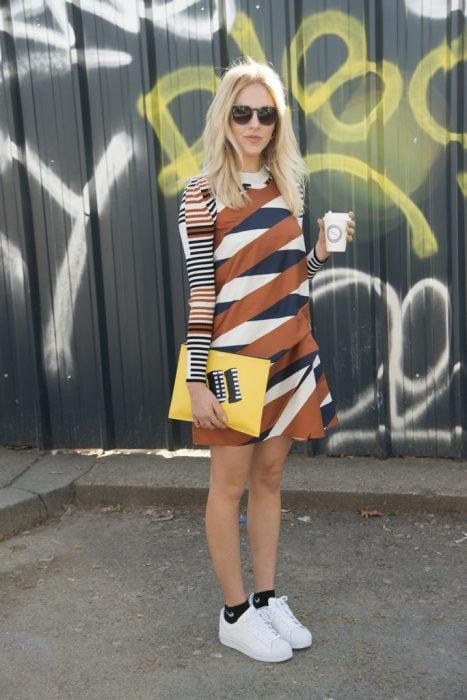 Mujer usando un vestido en color café con unas zapatillas en color blanco