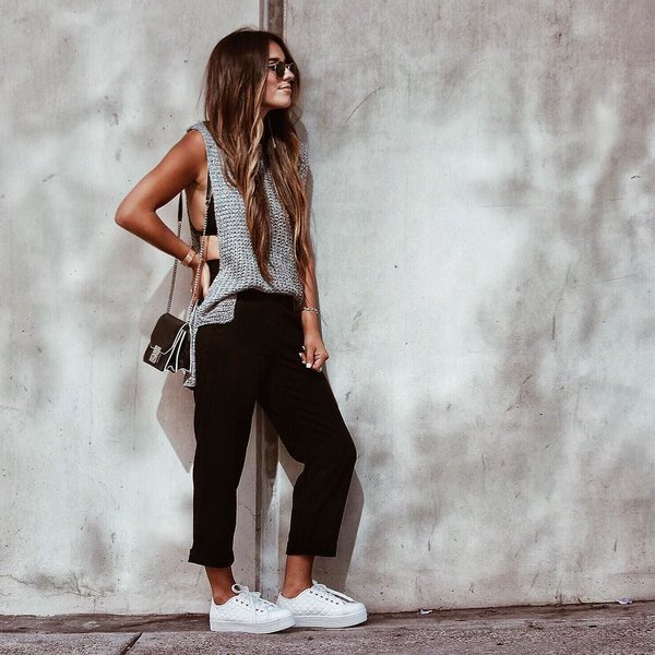 Chica usando una blusa de color gris, leggins y zapatillas de color blanco