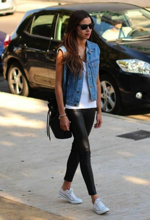 Chica usando unos leggins en color negro, blusa blanca, chaleco de mezclilla y zapatillas de color blanco