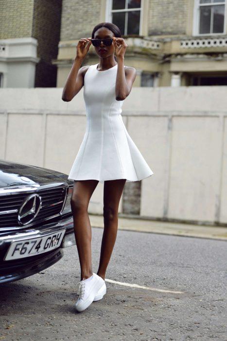 Chica usando un vestido en color blanco y zapatillas de color blanco