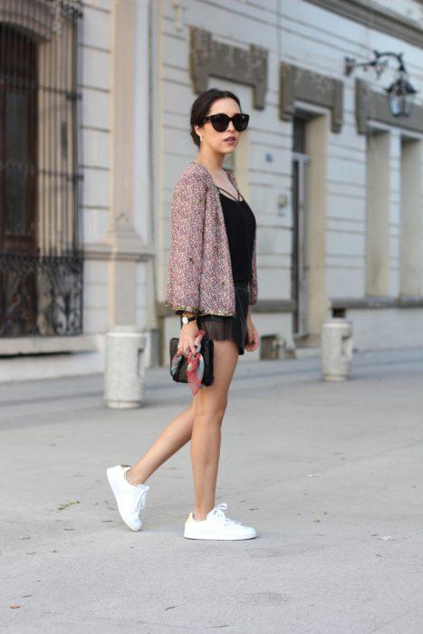 Chica usando un vestido en color negro y zapatillas de color blanco