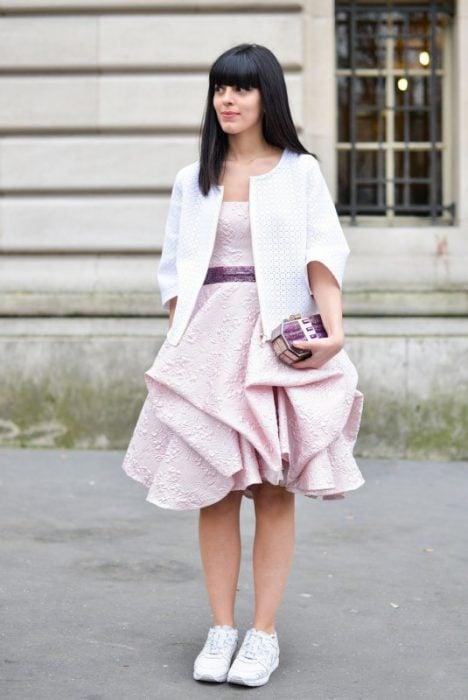 Chica usando un vestido en color rosa y unas zapatillas en color blanco
