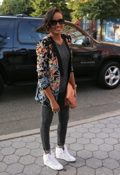 Chica usando un conjunto en color gris y zapatillas en color blancoi