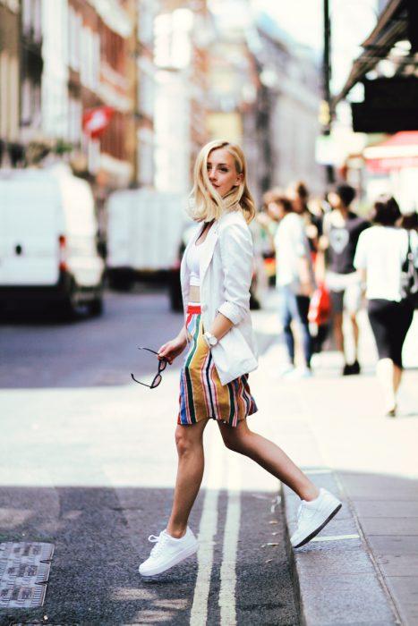 Chica usando un blazer blanco, zapatillas blancas y falda en color amarillo