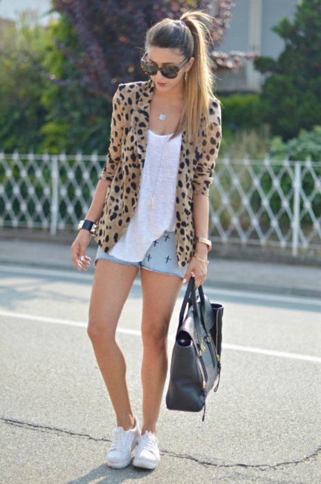 Chica usando un pantalón de mezclilla, blusa blanca, bluson animal print y zapatillas blancas
