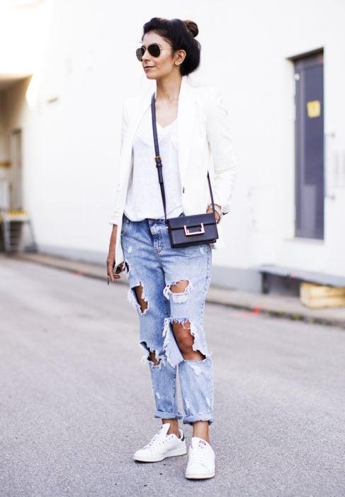 Chica usando pantalones en color azul rasgados, blazer y zapatillas en color blanco
