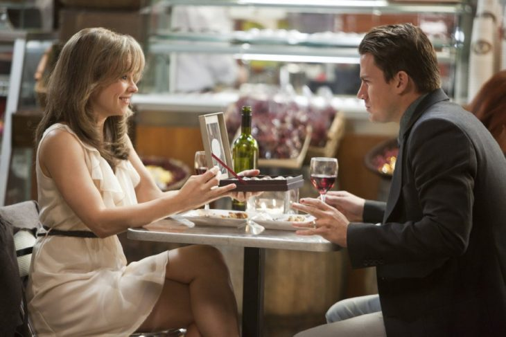 hombre sentado en una mesa y mujer sonríe