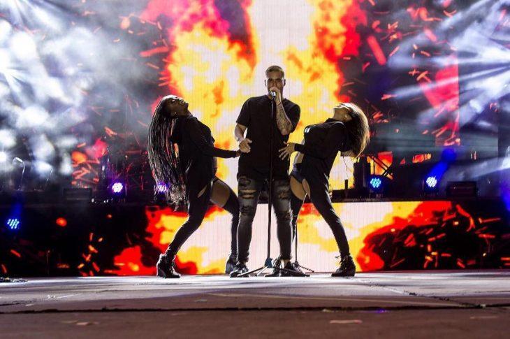 Maluma con dos mujeres en el escenario