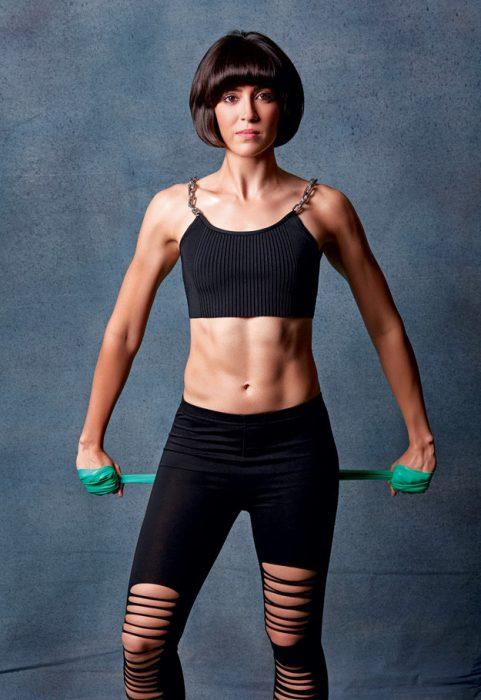 Mujer musculosa posando para la revista Elle en crop top y leggins