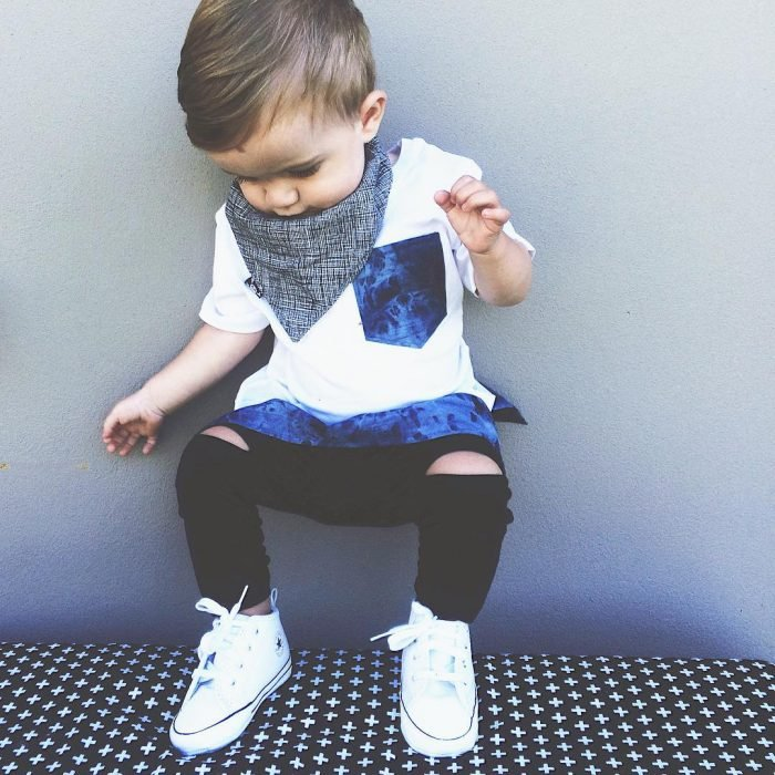 Bebé con pantalón negro y pañuelo en el cuello