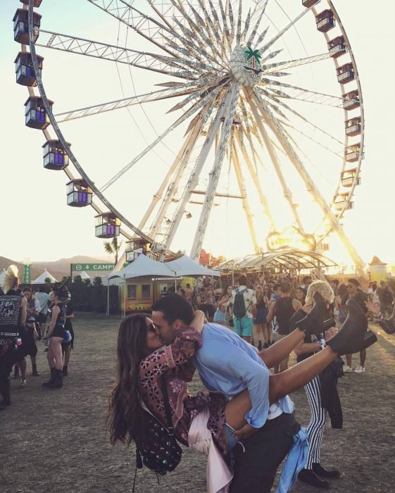 Pareja de novios besándose frente a un juego mécanico