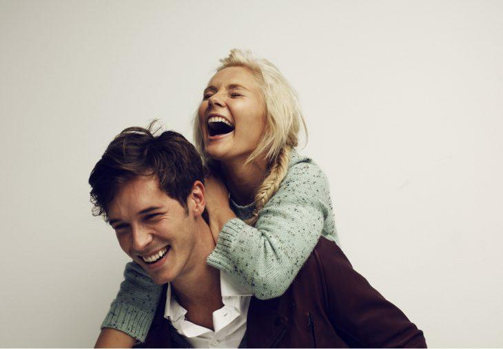 Pareja de novios riendo mientras ella está sobre sus espalda