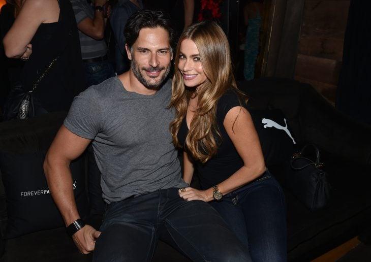 hombre sentado con camisa gris y mujer de cabello largo