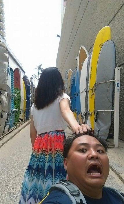 Chica tomando del cabello a su pareja mientras caminan por Hawai