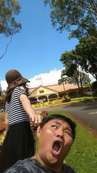 Chica tomando de una oreja a su pareja mientras caminan por Hawai