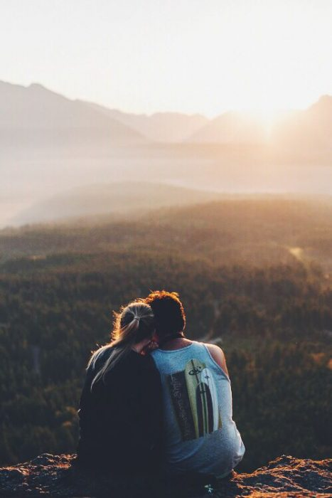 Pareja en una montaña viendo una puesta de sol