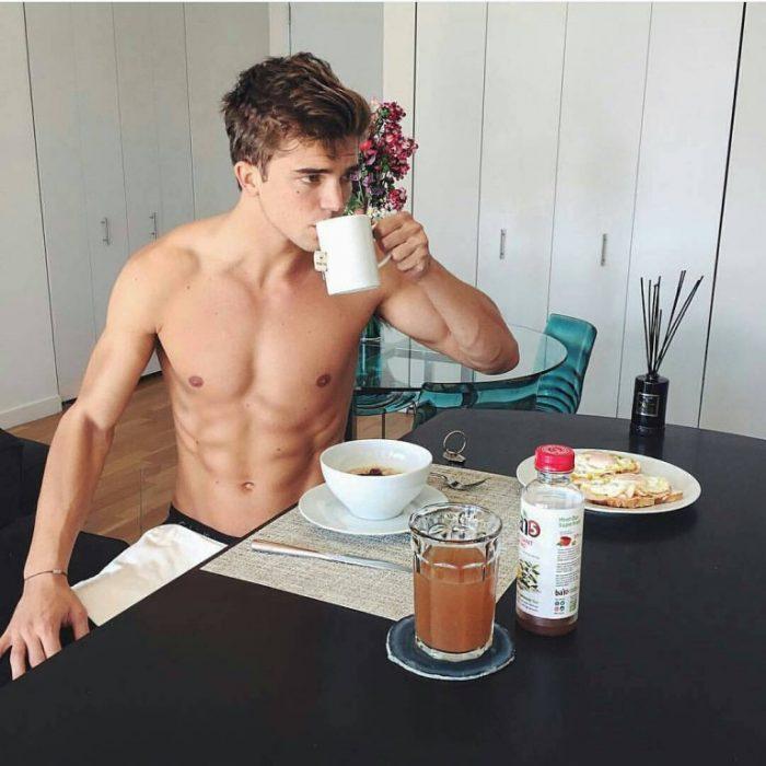 hombre musculoso sentado desayunando