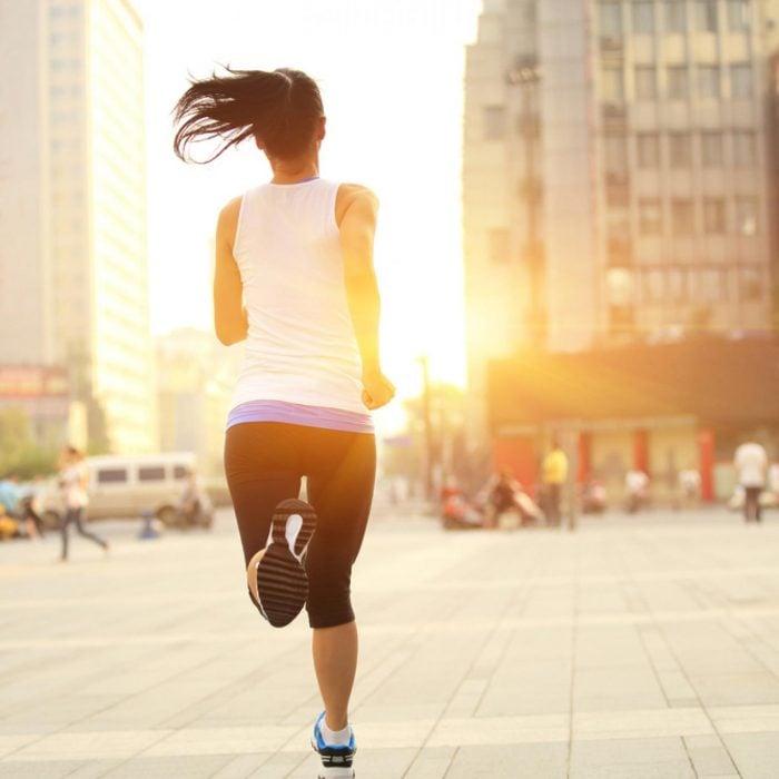 chica corriendo en la ciudad