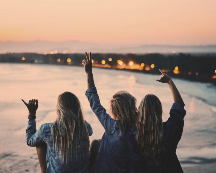 Chicas viendo el atardecer frente al mar