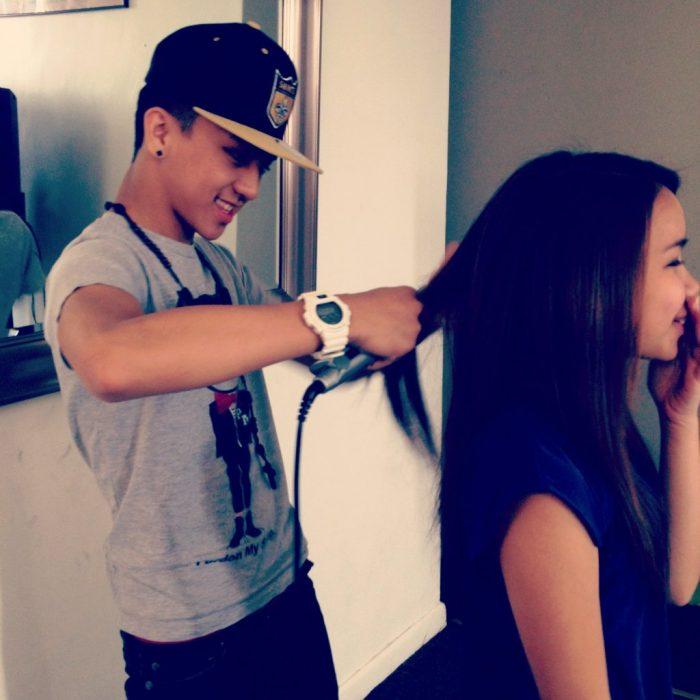 Chico planchando el cabello de una chica
