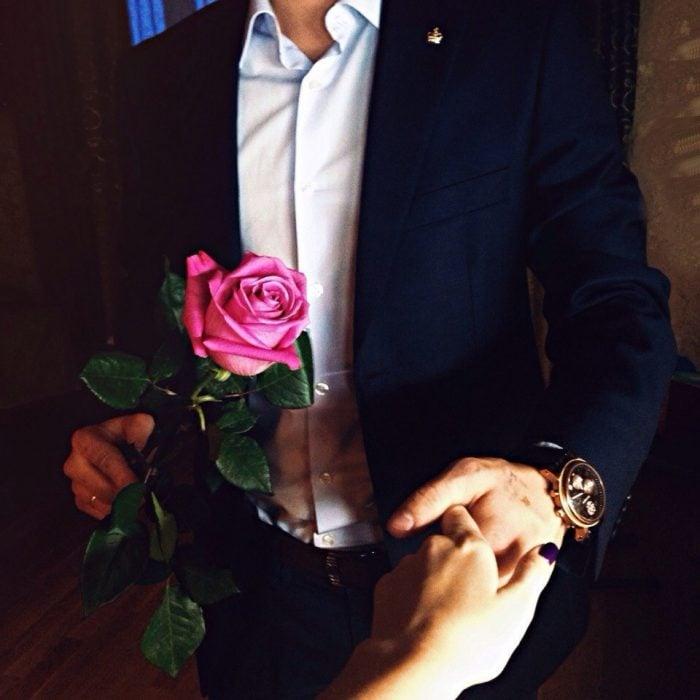 Chico con traje y rosa en la mano