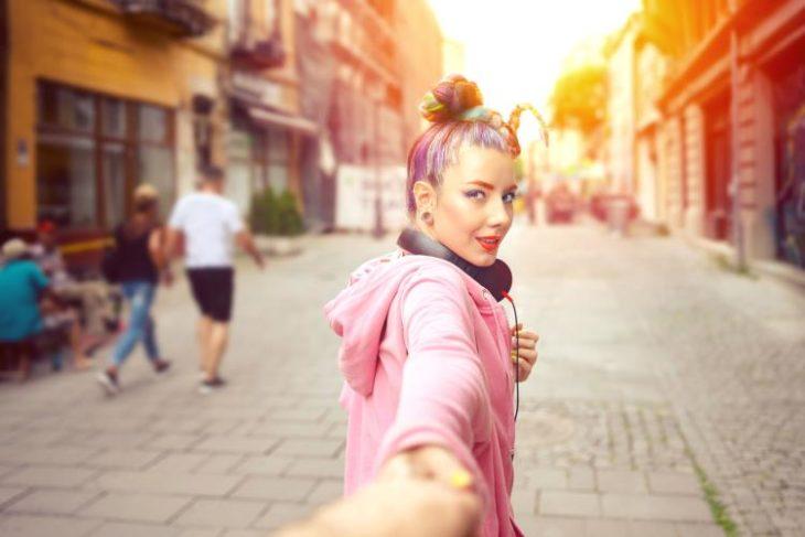 Chica caminando de la mano de su novio mientras ven una puesta de sol