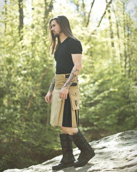 Hombre en medio del bosque parado sobre una piedra usando una falda escocesa y playera negra