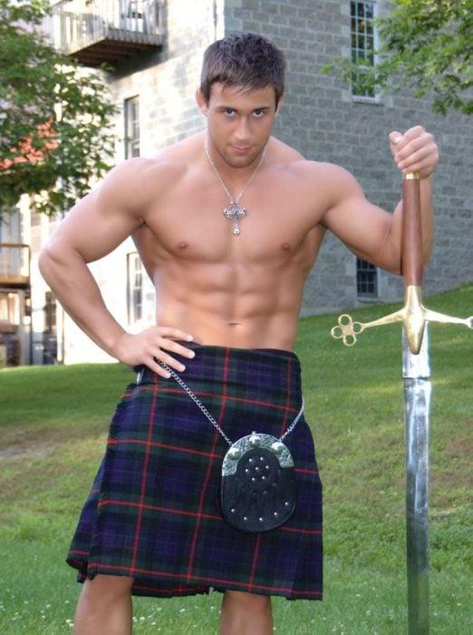 Hombre sosteniendo una espada mientras viste sólo una falda escocesa