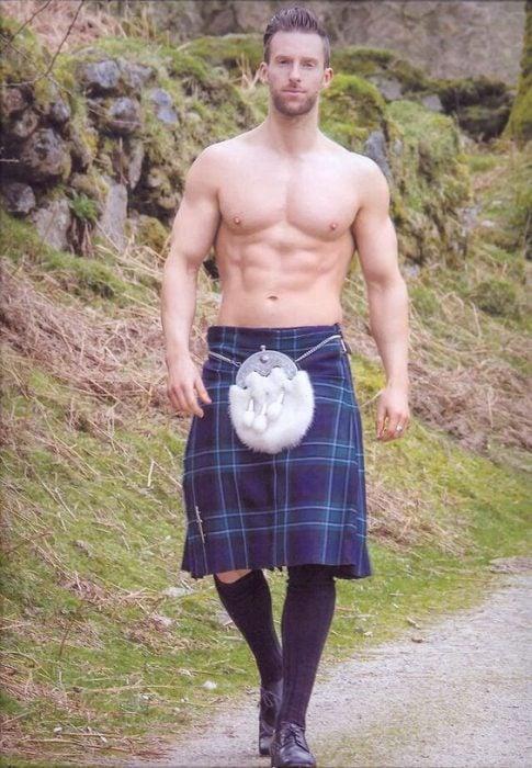 Chico caminando mientras usa sólo una falda escocesa