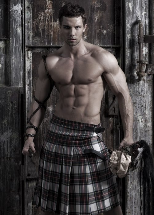 Chico recargado sobre una puerta sosteniendo un martillo mientras usa sólo una falda escocesa