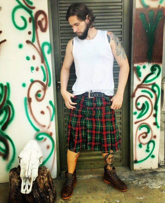 Chico con barba usando una falda escocesa