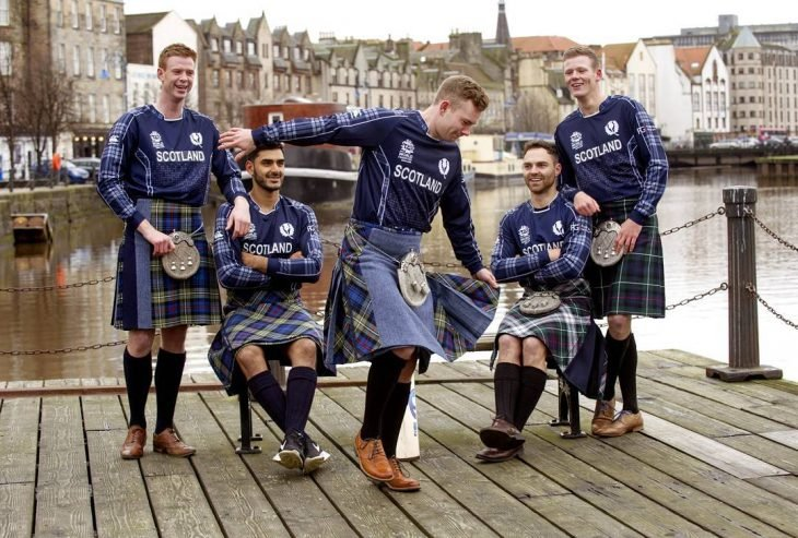 Chicos jugando fútbol usando una falda escocesa
