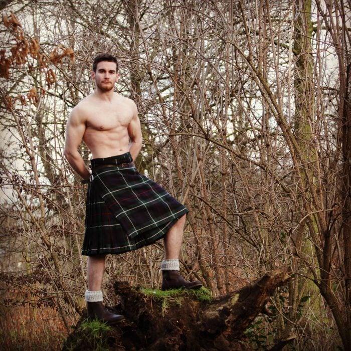 Chico parado sobre un árbol usando una falda escocesa
