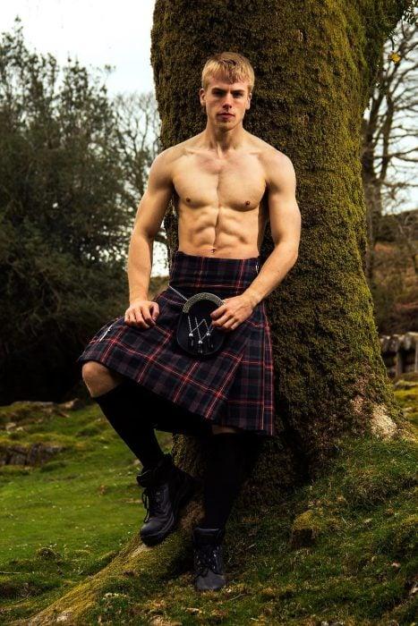 Chico recargado sobre un árbol usando una falda escocesa