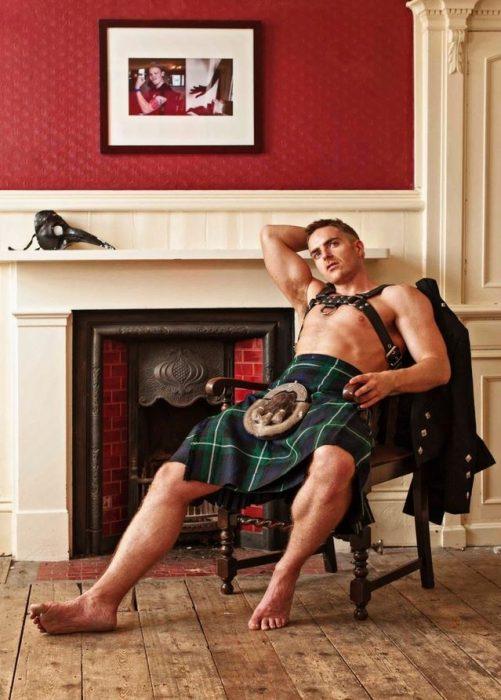 Chico sentado en una silla usando una falda escocesa