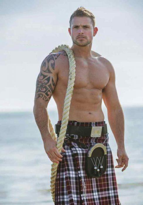 Chico sosteniendo una cuerda mientras usa una falda escocesa