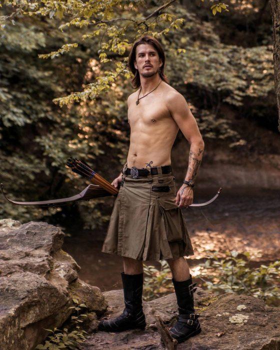 hombre sosteniendo un arco mientras usa sólo una falda escocesa