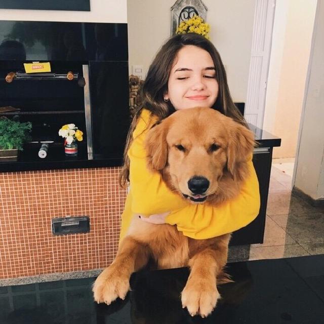 Chica abrazando perro golden
