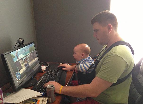 Hombre sosteniendo a un bebé mientras juega videojuegos