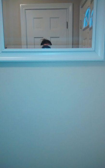 Chica intentando verse en un espejo