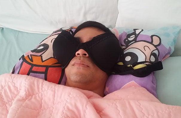 Chico durmiendo con un brasiere sobre su rostro