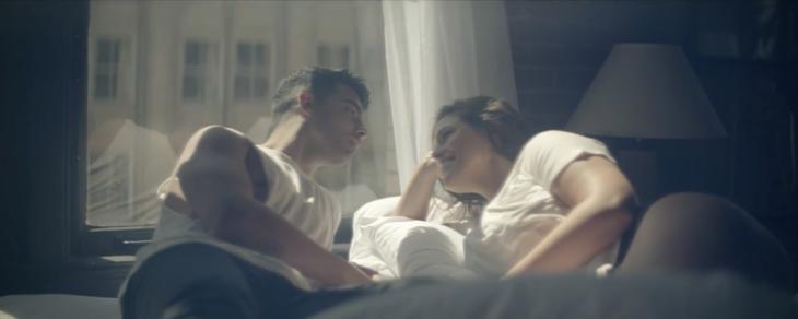 hombe sentado en una cama platica con mujer