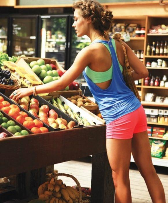 Chica en el supermercado comprando comida