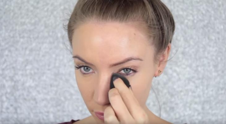 mujer rubia aplicando maquillaje en ojeras