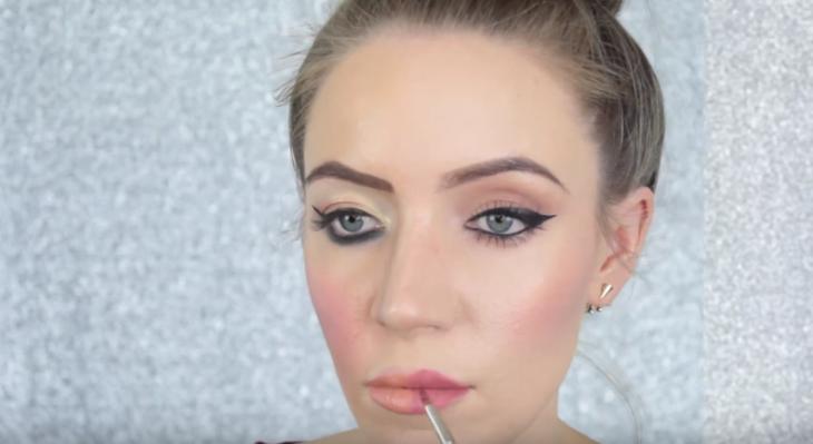mujer rubia pintandose los labios de color rosa
